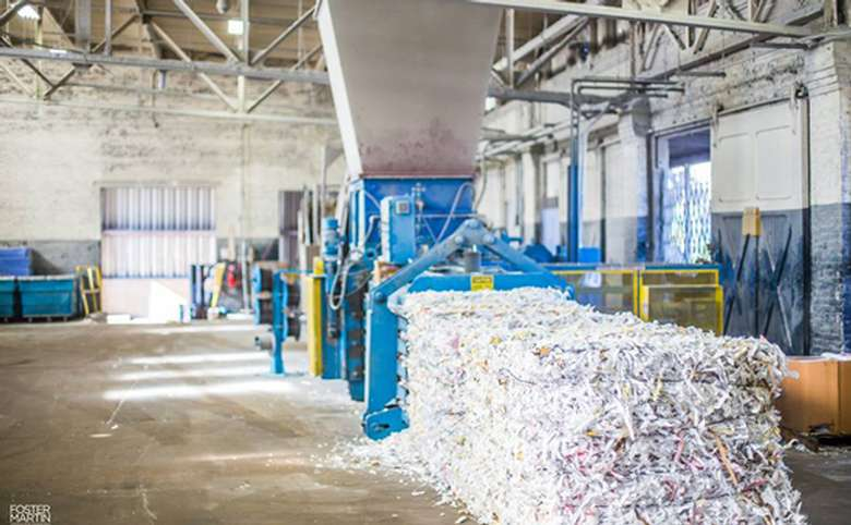 large shredding facility showing machinery and piles of shredded paper