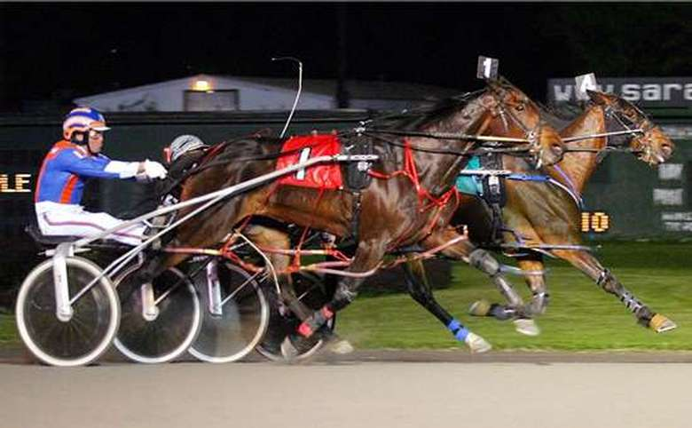 two horses and riders competing in harness racing