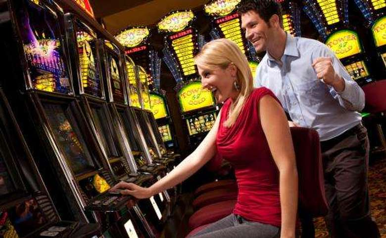 two people playing slot machines in a casino