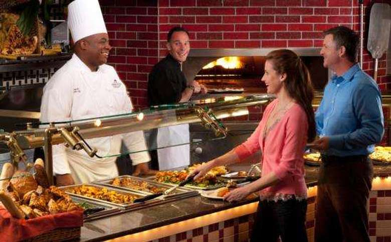 man and woman getting food from a buffet as the chef and another employee look on