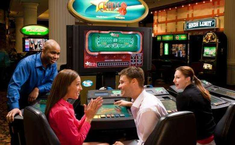 three people playing electronic craps in a casino