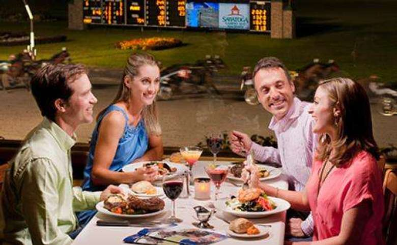 four people eating at a table overlooking the harness racing track