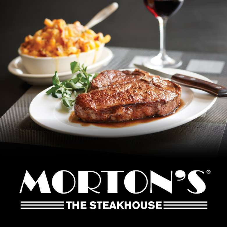 a large steak, side of macaroni and cheese, and a glass of red wine with morton's logo below
