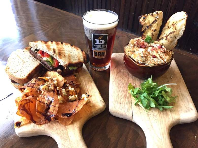 glass of beer and sandwiches and food on two wooden platters