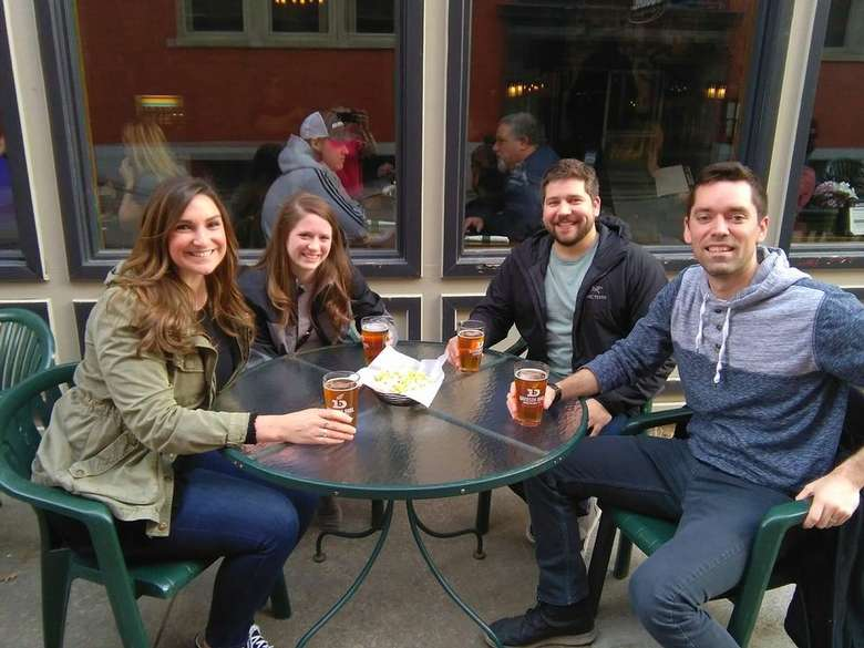 four people at a patio table with beer