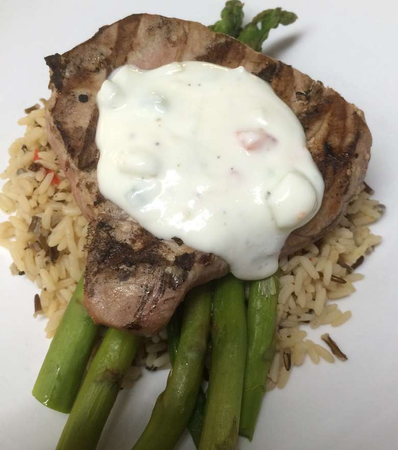 tuna steak with asparagus, rice, and a white sauce on top