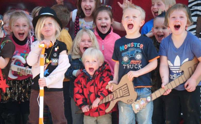 group of kids performing with cardboard and inflatable instruments