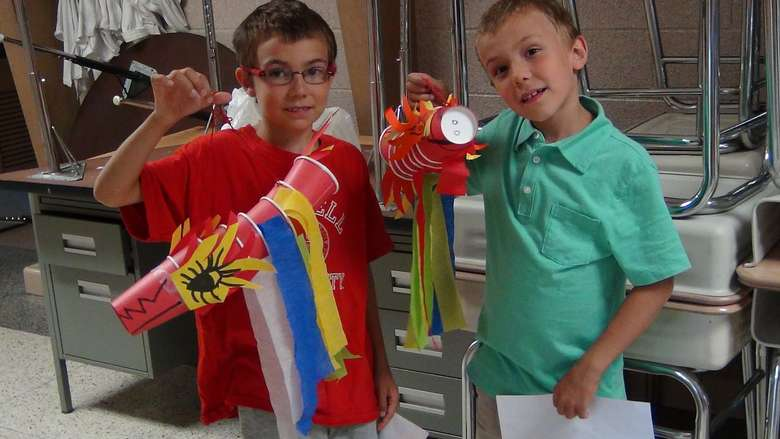 two boys holding up craft projects