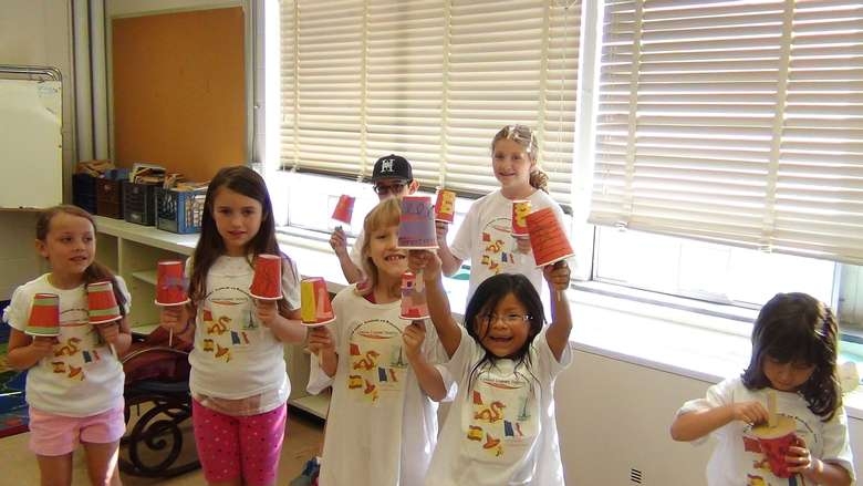 7 kids in matching t-shirts holding up cup crafts