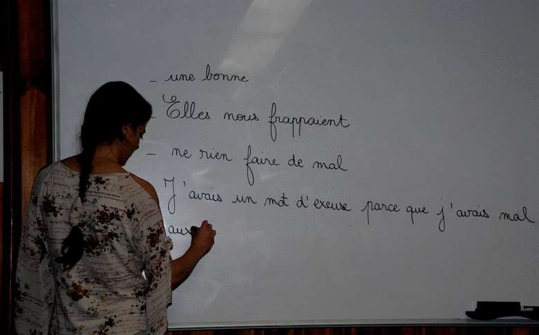 teacher writing in french on a white board