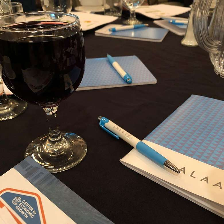 wine, notepads, pens on a table
