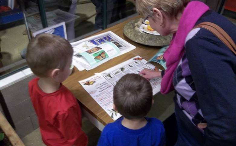 kids looking at science pamphlets