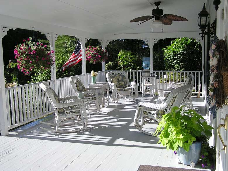 white chairs on a white deck with hanging plants