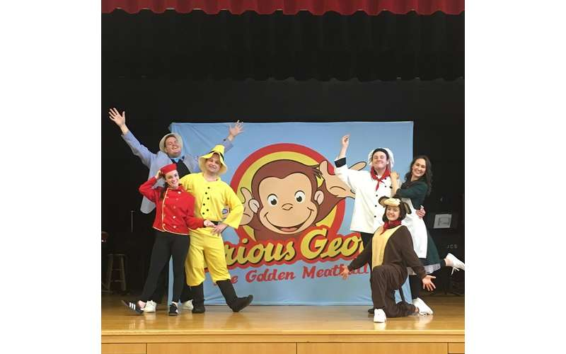 people on stage with curious George backdrop