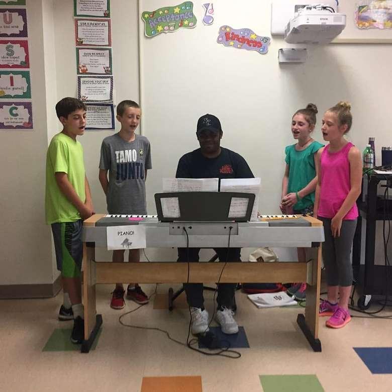 four kids singing around piano player