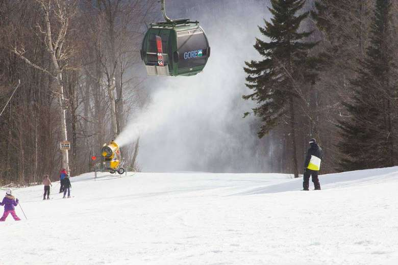 people skiing under the gondola at gore mountain while a snow gun sprays snow