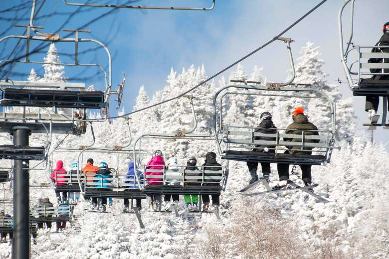 people riding up on a quad chairlift