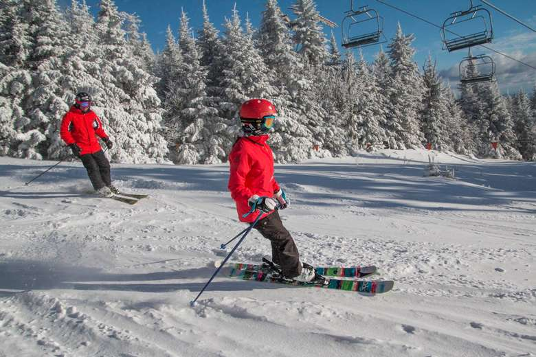 two skiers in red jackets skiing under a chairlift