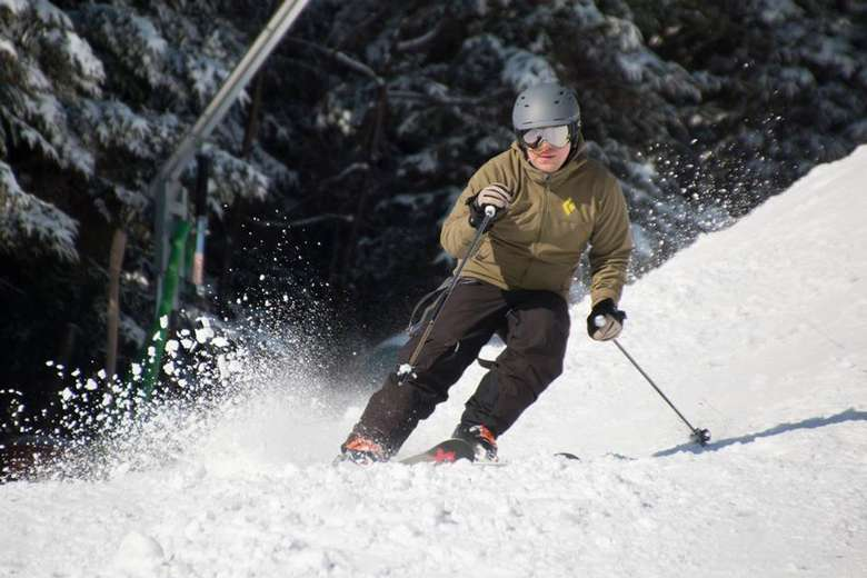 man in a brown coat skiing
