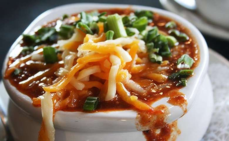 cup of chili with cheese and scallions