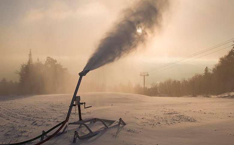 snow gun blowing snow at dawn