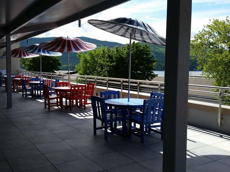 a few colorful patio tables and chairs with striped umbrellas