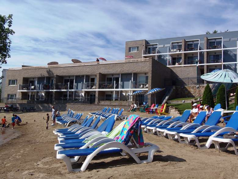 a large number of blue beach chairs on a sandy beach near a motel