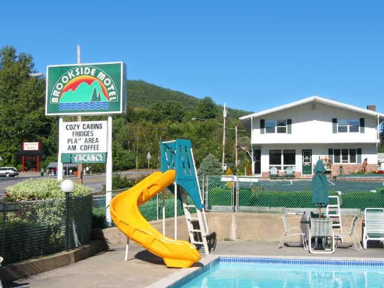 slide in front of pool, sign for motel
