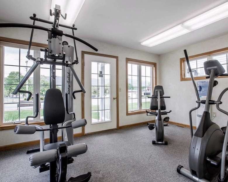fitness equipment in front of large windows and a door.