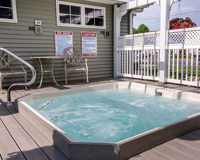 a bubbling hot tub, with a table and two chairs. There is a handle and steps down into the hot tub.