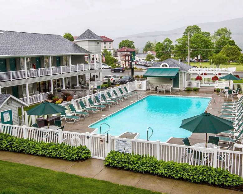 The exterior of the Quality Inn - Lake George, showing the inground pool, surrounding pool deck, and some of the rooms.