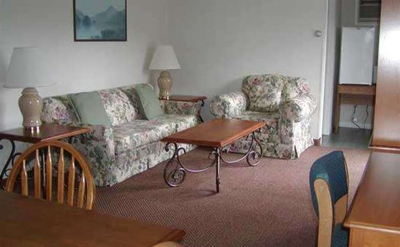 Another view of a motel room living area. There is an upholstered couch and chair, two end tables with lamps and coffee table. There is a table and chair, as well as a desk with a chair.