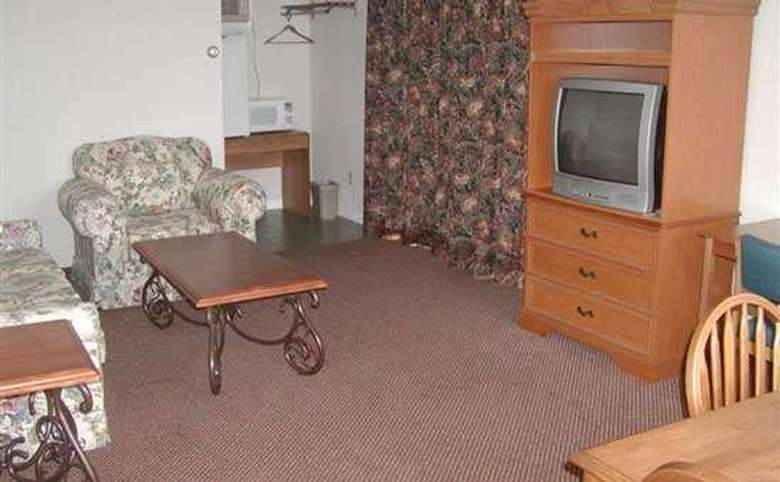 A living area in one of the motel rooms. There is an upholstered couch and chair with end table and coffee table. An armoire with three drawers holds a television. There is a small refrigerator and microwave to the rear of the room.