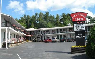 Outside view of the two-story motel. There are flowers in flower boxes along the railings on both levels. There is a sign that states Lake George Inn, Vacancy, Welcome, Heated Pool, WIFI, HBO, A.M. Coffee, 444 Canada Street.