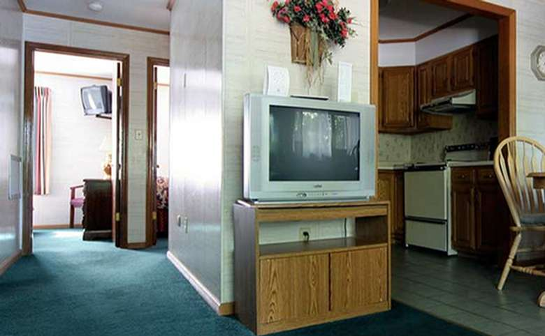 television, cabinet, and kitchen in a motel room