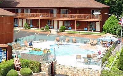 outdoor pool area surrounded by buildings at the mohican motel