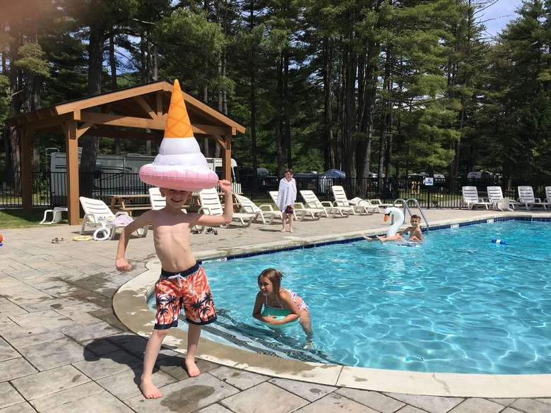 Boy with an ice cream floatie on his head by the pool