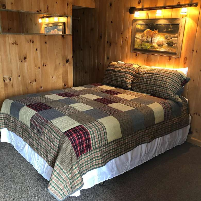 bed in a motel room with wooden walls