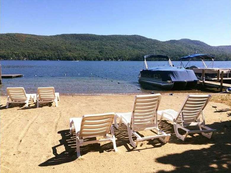 white beach chairs on the beach facing the lake