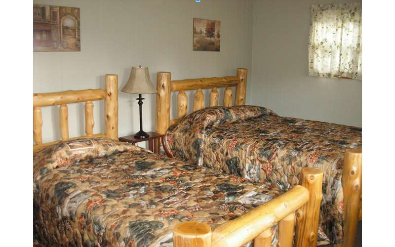 two twin size beds with a rustic frame and brown blankets