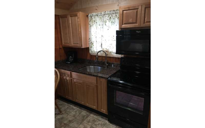kitchen with black stove and wood cabinets, window over sink