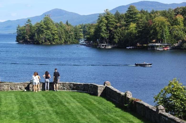 three people looking out at lake george on a lush green lawn