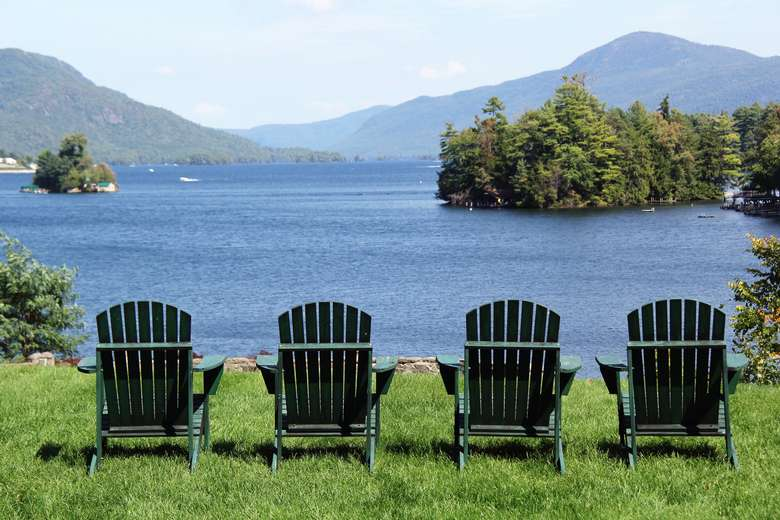 four green adirondack chairs overlooking lake george