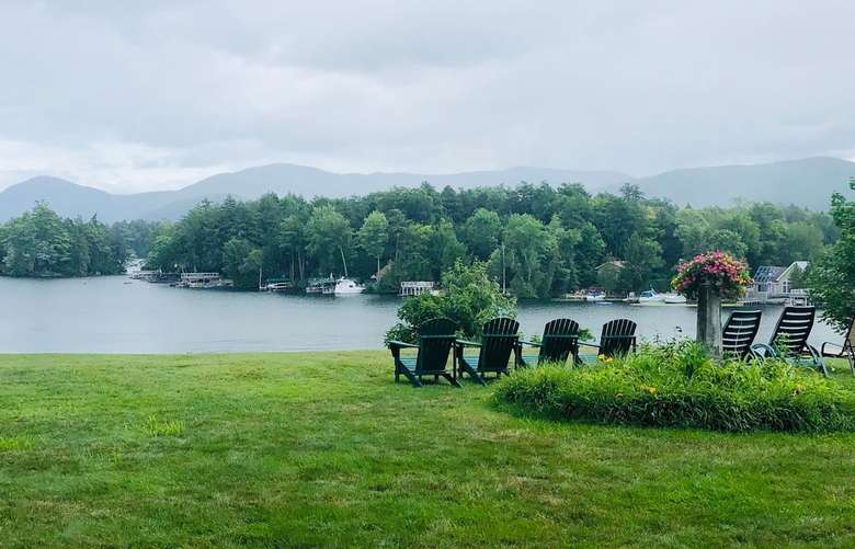 four Adirondack chairs overlooking a lakeside view.