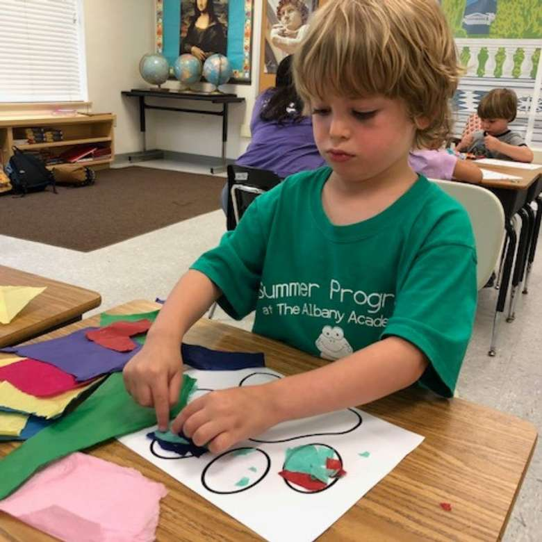a boy working on a craft on a desk