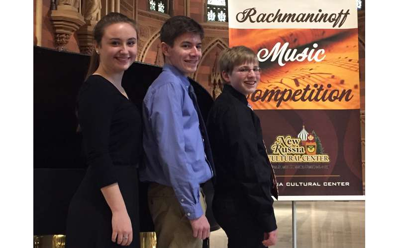 Three young adult musicians posing after a music competition.