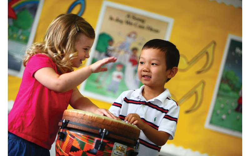 young boy and girl playing drums