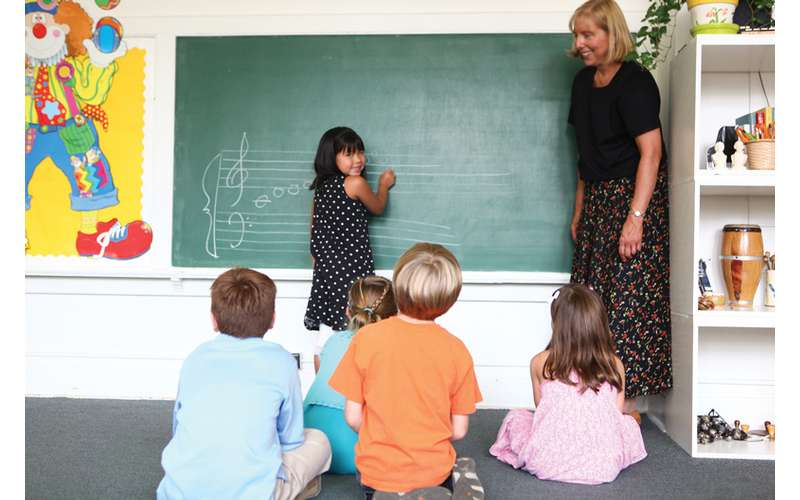 students listening to a teacher speak by a chalkboard