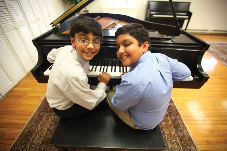 two boys playing piano