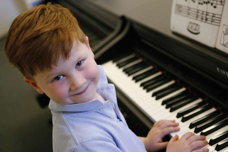 young boy smiling by a piano